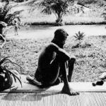 Мужчина смотрит на руки своей пятилетней дочери, отрезанные в наказание за плохо выполненную работу по сбору каучука.